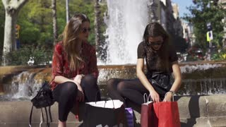 Women talking and sitting on fountain, slow motion shot at 120fps