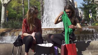 Women talking and sitting on fountain, slow motion shot at 240fps