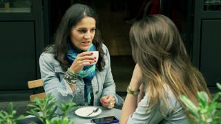 Women talking in the street cafe and drinking coffee, steadycam shot