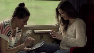 Women traveling by train and using electronics, steadycam shot