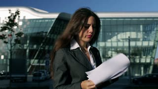 Worried businesswoman looking on paper outside, steadycam shot
