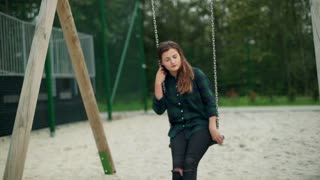 Worried girl swinging on the seesaw and looking to the camera