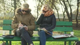 Worried girl talking on cellphone while her boyfriend doing homework