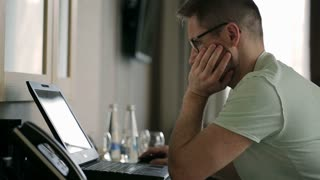 Worried man sitting at the desk and working on laptop