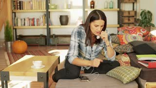 Worried woman sitting in her living room and thinking about something