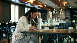 Worried woman using smartphone in the restaurant
