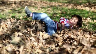 Young boy playing in autumn park, steadycam