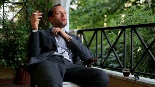 Young businessman after hard work drinking and smoking cigarette on his balcony