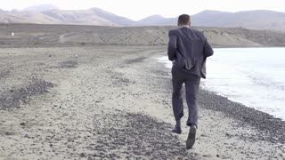 Young businessman jogging on the beach, slow motion shot at 240fps