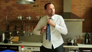 young businessman tying his tie and finishing breakfast in the kitchen