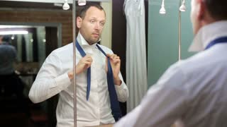 young businessman tying his tie and looking in the mirror