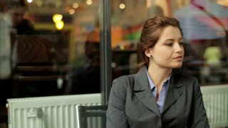 Young businesswoman sitting in restaurant and looking around, outdoors