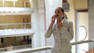 Young businesswoman talking on cellphone in the office hall, steadycam shot