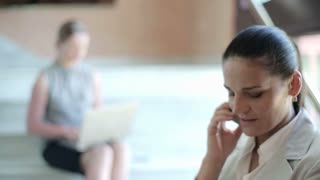 Young businesswoman with smartphone in the office hall