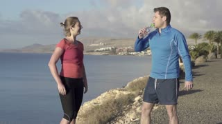 Young couple drinking water while jogging on the beach, slow motion 240fps