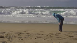 Young couple jogging on the beach, man resting, slow motion shot at 240fps