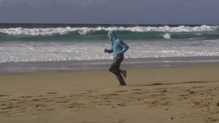 Young couple jogging on the beach, man resting, slow motion shot at 60fps