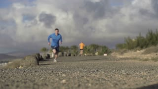 Young couple jogging on the beach, slow motion shot at 120fps