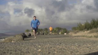 Young couple jogging on the beach, slow motion shot at 60fps