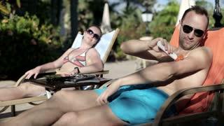 Young couple lying on sunbed and applying sun cream