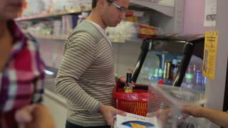 Young couple paying for shopping in supermarket, steadicam shot