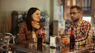Young couple sitting in a pub at night and drinking beer
