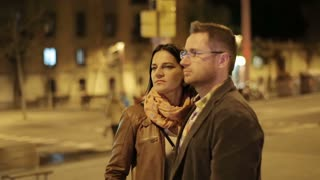 Young couple standing and looking around in night city, steadycam shot