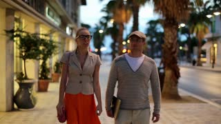 Young couple walking along shopping arcade in the evening