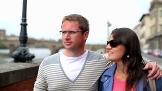 Young couple walking near river in the city, steadycam shot