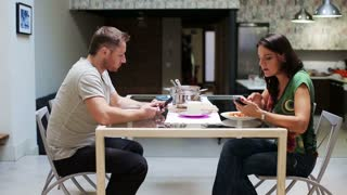Young couple with cellphones eating dinner at home