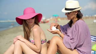Young female friends applying sunlotion on the beach
