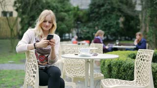 Young girl using smartphone and smiling to the camera in the garden