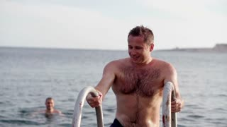 Young man after swimming in the sea, slow motion shot at 120fps