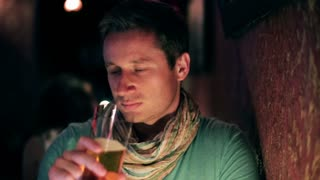 Young man drinking beer in a pub, steadycam shot