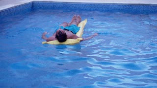 Young man floating on a mattress in swimming pool, slow motion shot at 240fps