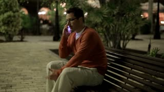 Young man getting bad news by cellphone in tourist resort in the evening
