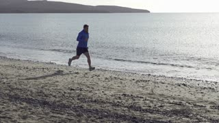 Young man jogging on the beach, slow motion shot at 240fps