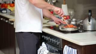 Young man preparing dinner in his kitchen, steadicam shot
