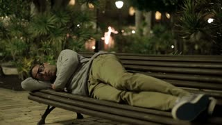 Young man sleeping on bench in tourist resort at night