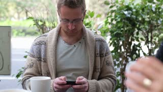 Young man texting message on cellphone in the restaurant