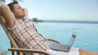 Young man with laptop relaxing by swmming-pool in hotel, steadicam