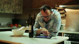 Young man with tablet computer drinking wine in the kitchen