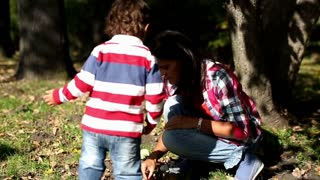 Young mother playing with her son in autumn park, slow motion