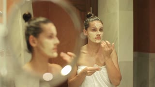 Young woman applying face mask in front of mirror