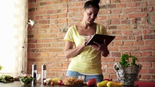Young woman checking recipe on tablet computer before cooking