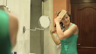 Young woman combing her hair in front of mirror