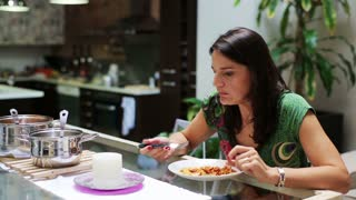 Young woman eating dinner at home