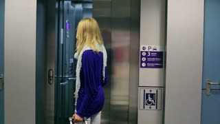 Young woman entering elevator and holding luggage