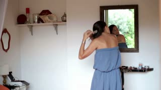 Young woman hair brushing in front of the mirror