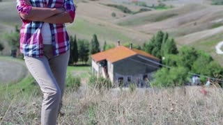 Young woman in front of her beautiful house in Tuscany, crane shot